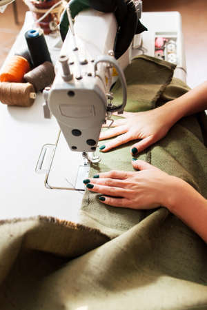 sewing machines: seamstress sews clothes. Workplace of tailor - sewing machine, rolls of of thread, scissors.