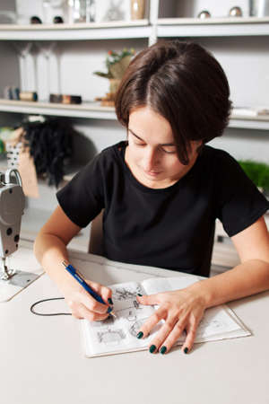 needlewoman: Seamstress creates a sketch in the working notebook. designer draws the clothes and bags.