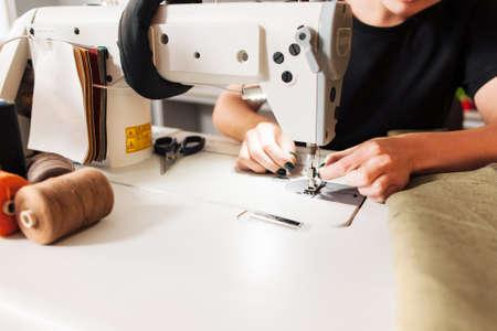 仕立て屋の服を縫うし、針でスレッドを置きます。糸、生地、はさみの仕立て屋 - ミシンの職場のロールします。 写真素材