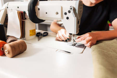 seamstress sews clothes and put thread in needle. Workplace of tailor - sewing machine, rolls of of thread, fabric, scissors. Imagens - 52171906