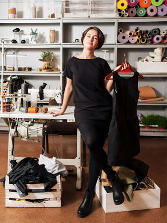young clothing designer demonstrate the ready-made model of dress. Portrait of a professional in interior of sewing workshop.