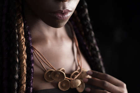 ace of unrecognizable afro-american woman with ethnic hairstyle. Her neck wrapped with colored long braids Stock Photo