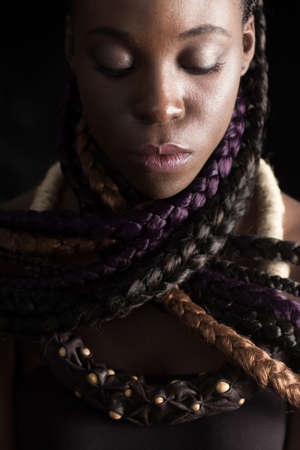 dark skinned: ace of  afro-american woman with ethnic hairstyle. Her neck wrapped with colored long braids
