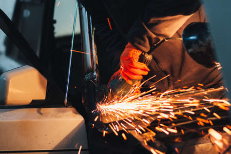 A construction worker using an angle grinder producing a lot of sparks. Professional metall work
