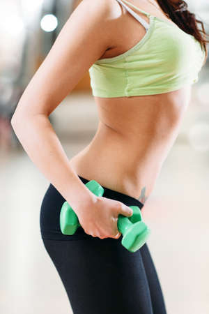 taut: slim girl with green dumbbells at the gym.  Fit belly, taut abdominal muscles Stock Photo