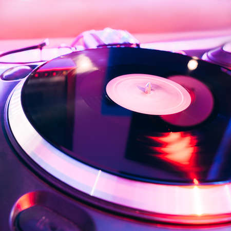 turntable: Closeup of turntable playing vinyl deck in nightclub light with nobody Stock Photo