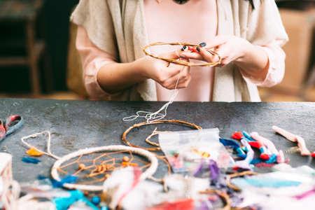 craftswoman은 예술 스튜디오에서 바느질 액세서리 드림 캐쳐를 만듭니다. 워크숍 테이블과 손에 측면보기입니다.