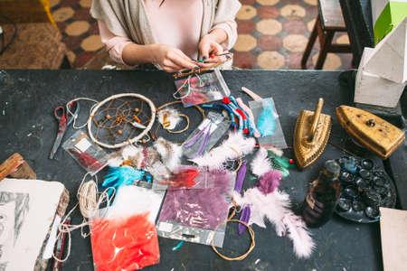 atrapasueños: artesana hace nueva Dreamcatcher de accesorios de costura en el estudio de arte. Vista superior en la mesa de taller y manos. Lío en Workplase