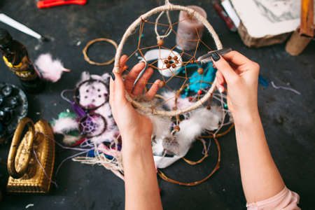 craftswoman: craftswoman makes Dreamcatcher of sewing accessories. top view on workshop table and hands.