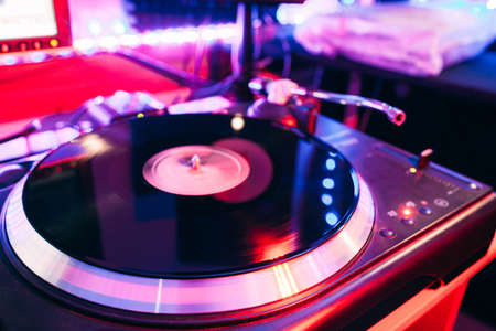 turn table: Closeup of turntable playing vinyl deck in nightclub light with nobody Stock Photo