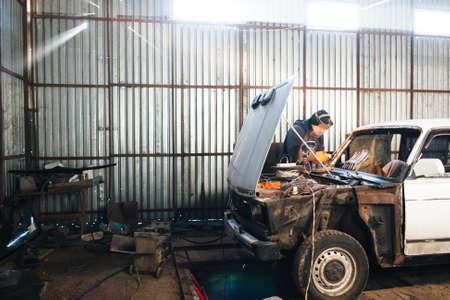 古い破損した自動車のサービス ステーション。ボディワークと復元のボディとエンジン区画。ワーク ショップの背景