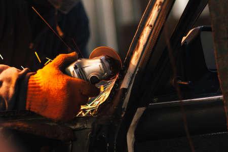 Mécanicien de faire un travail du métal, la réparation automobile avec broyeur électrique. Concept de rénovation de la vieille voiture et un service de garage Banque d'images - 54301932