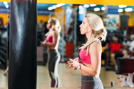 beautiful athlete looking with fear at the punching bag. Newcomer in the gym