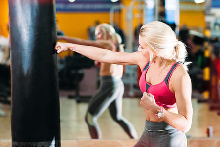 strongly: beautiful athlete strongly hits punching bag. Newcomer blonde in the gym