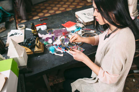 craftswoman: craftswoman makes Dreamcatcher of sewing accessories  in art studio. this series have lot of colorful photos about how to make dream catchers Stock Photo