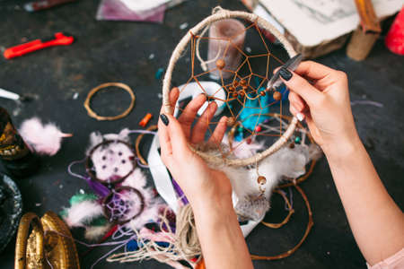 atrapasueños: artesana hace Dreamcatcher de accesorios de costura. vista desde arriba en la mesa de taller y manos. Foto de archivo
