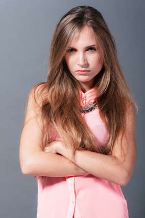 offend: Angry girl shows her negative emotions.udio photo on a gray background