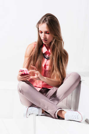communicates: The girl uses the new features of her phone. Young woman sends sms and communicates Stock Photo