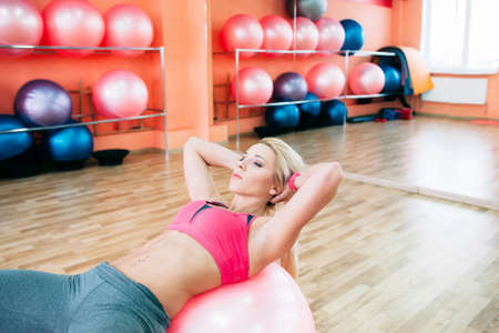 young woman doing strength workout. Athlete strain her abs and training her endurance and rower Stock Photo