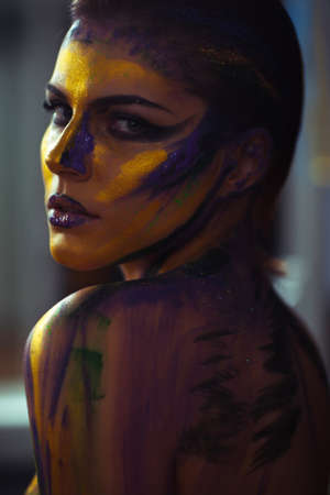 nude girl young: Creative body art make-up painted on a woman in yellow and purple colors against a grey background