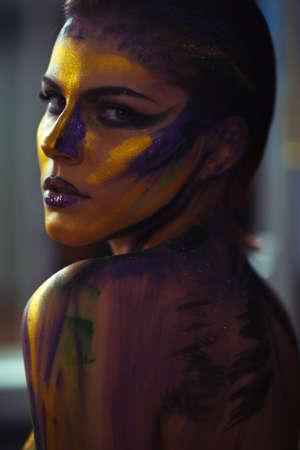 junge nackte m�dchen: Kreative Kunst am K�rper Make-up auf einer Frau gemalt in gelb und lila Farben vor einem grauen Hintergrund