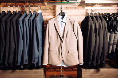 Many mens business suits of different colors. Modern boutique with clothes for business people. Horizontal photo