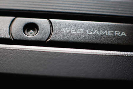 hack: Web camera close up on black laptop monitor. Spy camera (phishing, hack) concept Stock Photo