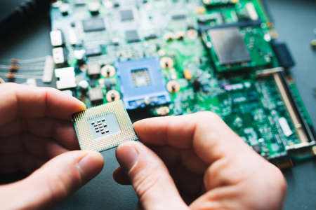 microprocessor: Technician analysis and plug in CPU microprocessor to motherboard socket. Workshop background Stock Photo