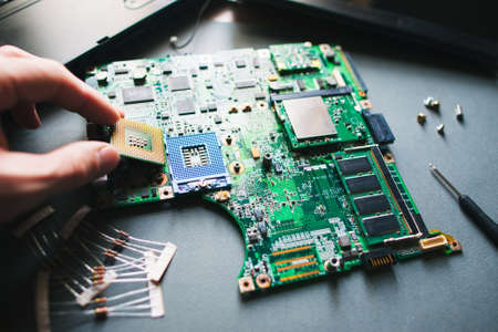 Technician analysis and plug in CPU microprocessor to motherboard socket. Workshop background Imagens