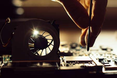 Ingénieur réparation ordinateur (pc) planche. bouchon de technicien dans les composants électroniques sur la carte mère.