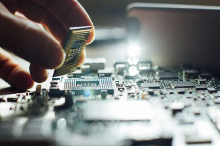 Technician plug in CPU microprocessor to motherboard socket. Workshop background Stock Photo