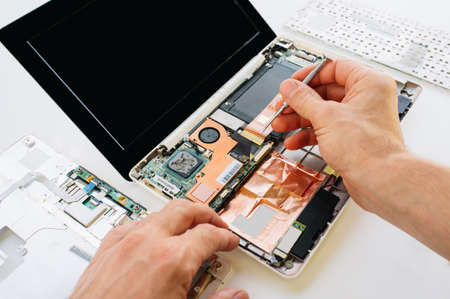 The engineer repairs the laptop (pc, computer) and the motherboard. Installs the equipment (cpu)