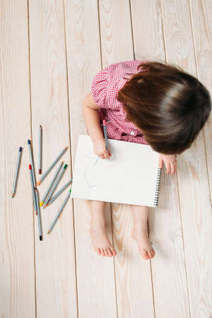 baby sit: Unrecognizable child learns to draw with colored pencils. Girl sitting on the wooden floor and draw simple drawings.