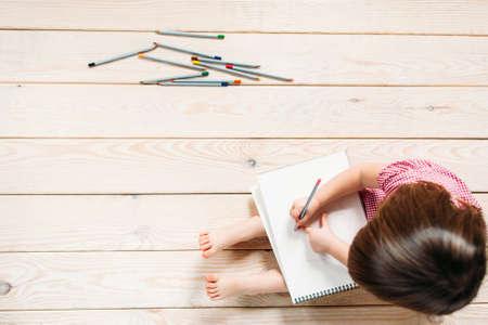 인식 할 수없는 아이 컬러 연필로 그리는 배운다. 소녀는 나무 바닥에 앉아 간단한 그림을 그립니다. 스톡 콘텐츠