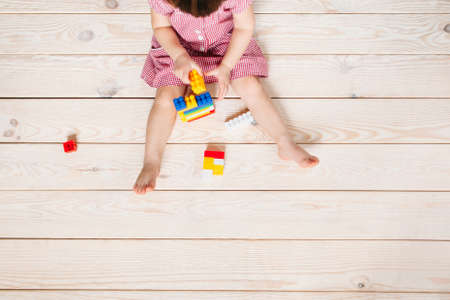 little girl in red dress sitting on the wooden floor and playing Lego. Top view