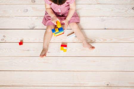 klein meisje in een rode jurk zittend op de houten vloer en het spelen van Lego. bovenaanzicht