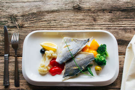 Dorado fillet with little stewed vegetables on a white square plate. boiled fish fillets with a garnish of vegetables. lenten food. Lenten food served on a wooden background