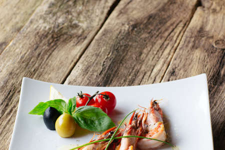 free space: Mediterranean cuisine on wooden background with free  space. Mediterranean cuisine from seafood. Grilled tiger shrimps with fresh mediterranean vegetables. Stock Photo