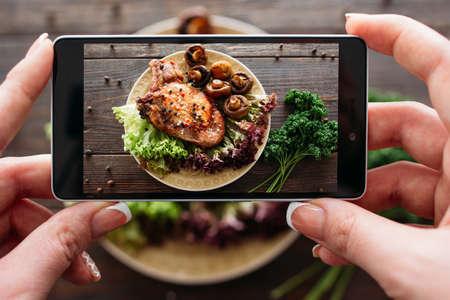 신선한 야채와 구운 돼지 고기의 음식 사진입니다. 홈 소셜 네트워크를위한 음식 사진을했다. 구운 고기의 상위 뷰 휴대 전화 사진.