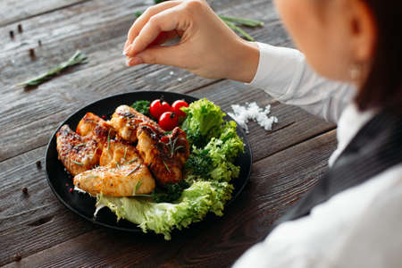 Preparation of chicken wings on wooden table. Chief cooks grilled spicy chicken with fresh vegetables. Over the shoulder view of food preparation. Imagens