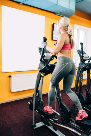 eliptica: Fitness girl on cardio workout. Cardio workout in gym. Athletic girl working out on elliptical machine.