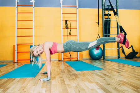 pushup: Fitness girl training trx push-up in gym. Fitness coach show trx pussh-up in gym. Athletic girl working on trx in gym Stock Photo