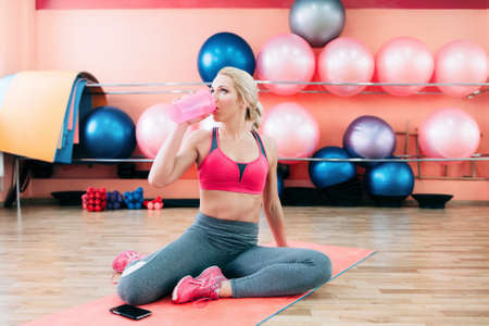 Girl drinking protein shake after training. Sporty woman sitting on yoga mat after some exercises drinks protein shake. Sporty girl sitting on yoga mat after some exercises drinks sports nutrition.
