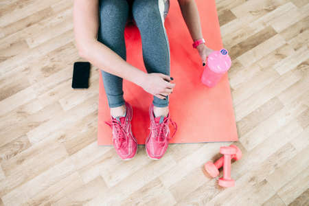 フラット横たわっていたスポーツ写真。女性アスリートはトレーニングの後リラックスします。平らフィットネス トレーニング後コーチの写真を置