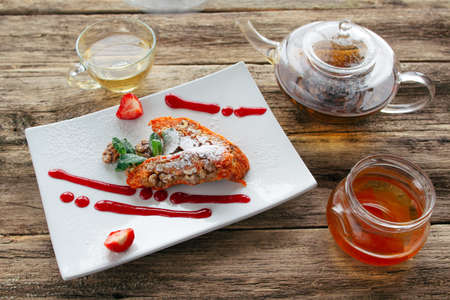 Healthy vegetable dessert. Carrot apple  sweet pie with a mango jam and a pot of herbal tea served on wooden background. Healthy vegetable dessert for vegeterian or lent.