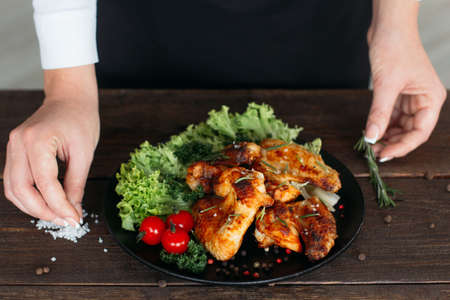 a portion: Top view of food decoration on wooden table. Chief presents grilled spicy chicken. Decorating chicken wings with lettuce and tomatoes cherry. Stock Photo