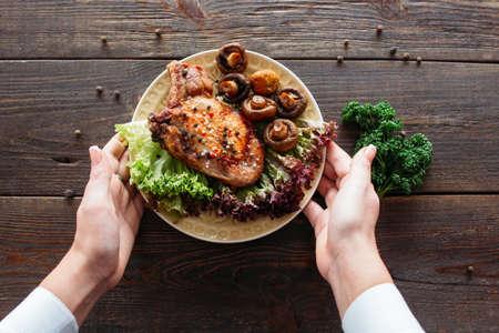 ウェイターは、レタスとキノコと鶏料理を提供します。チーフは、小さなカフェでのプレゼンテーションのための食糧を飾るします。ウェイターは