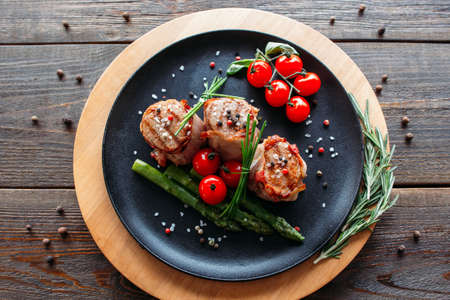 Grilled pork dish with fresh vegetable spices. Food photographyof grilled pork medallions with herbs and spices. Tasty cook meat with  vegetables on dark wooden background. Stock Photo