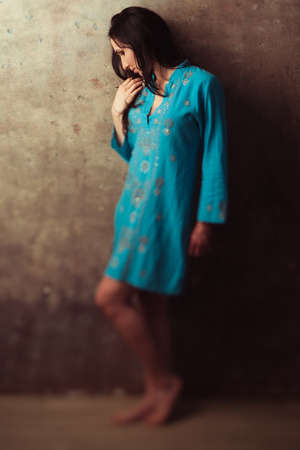 submissiveness: Upset indian girl in blue dress standing against stone background. Offended upset indian girl against wall. Disappointed east girl in blue dress.