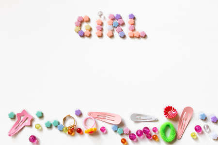 Little girl accessories lifestyle set on  white background.  Many little girl accessories scattered on blank white paper - beads, hair clips, rings. There are the inscription Girl on the top of image Stock Photo